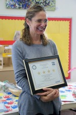 Teacher holding 4 star certificate.